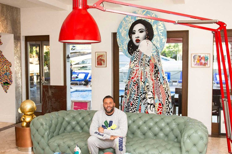 Grutman in his living room, adorned with a Hush sculpture, a Nicolas Party painting, leather couches, and a giant Baxter lamp.