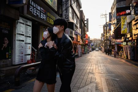 People wearing face masks amid concerns over the COVID-19 novel coronavirus, walk through an alleyway in Seoul on Marh 24, 2020. (Photo by ED JONES/AFP via Getty Images)