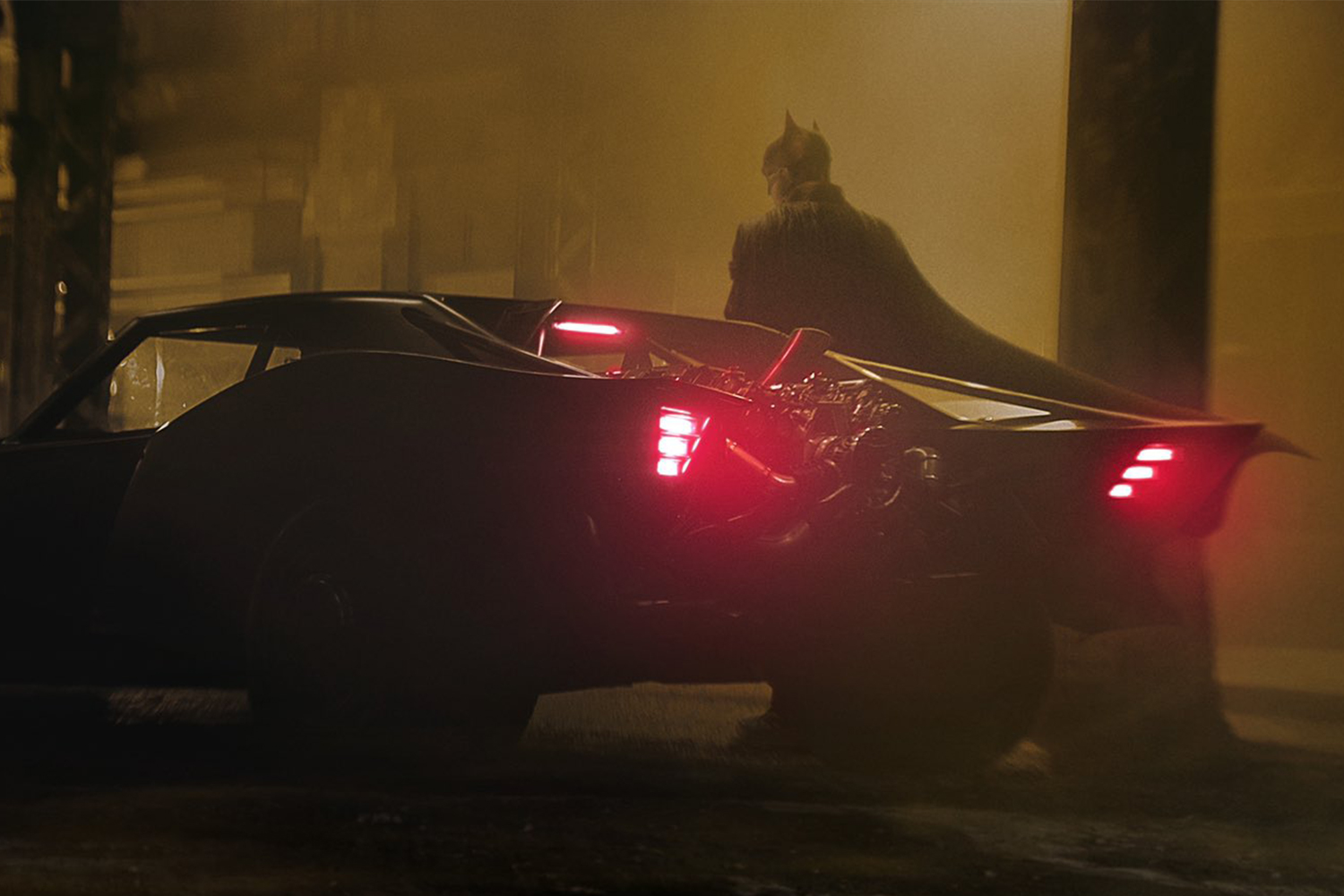 Batman standing next to the new Batmobile
