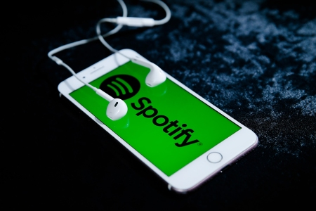 iPhone smartphone with headphones playing Spotify