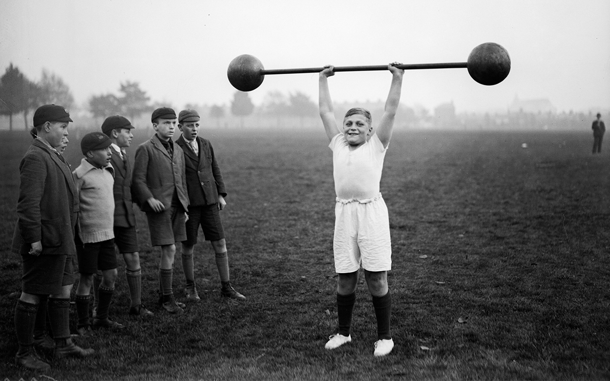 "A young fellow lifting a barbell in the 1930s. Is he ""stunting"" his growth?"