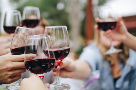 Group of drinkers holding up glasses of red wine