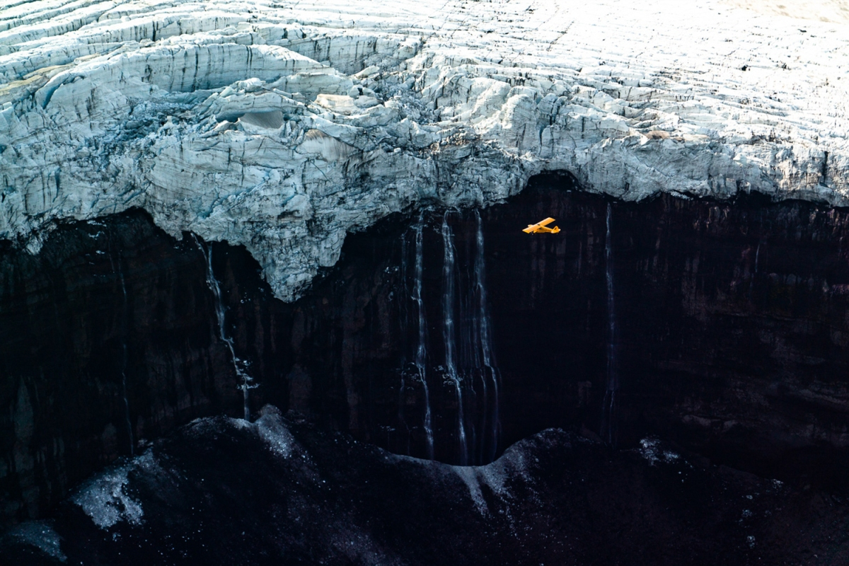 A yellow Cessna flys by Icelandic glaciers