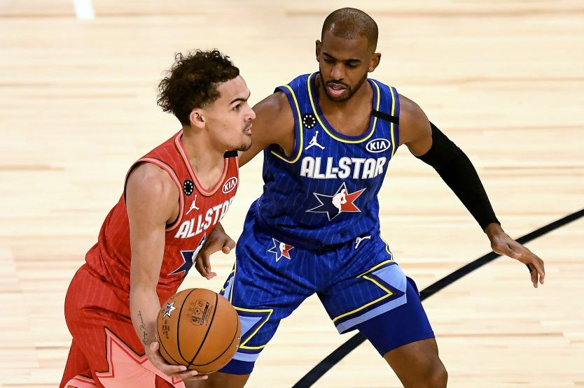 Trae Young dribbles the ball while being guarded by Chris Paul. (Stacy Revere/Getty)
