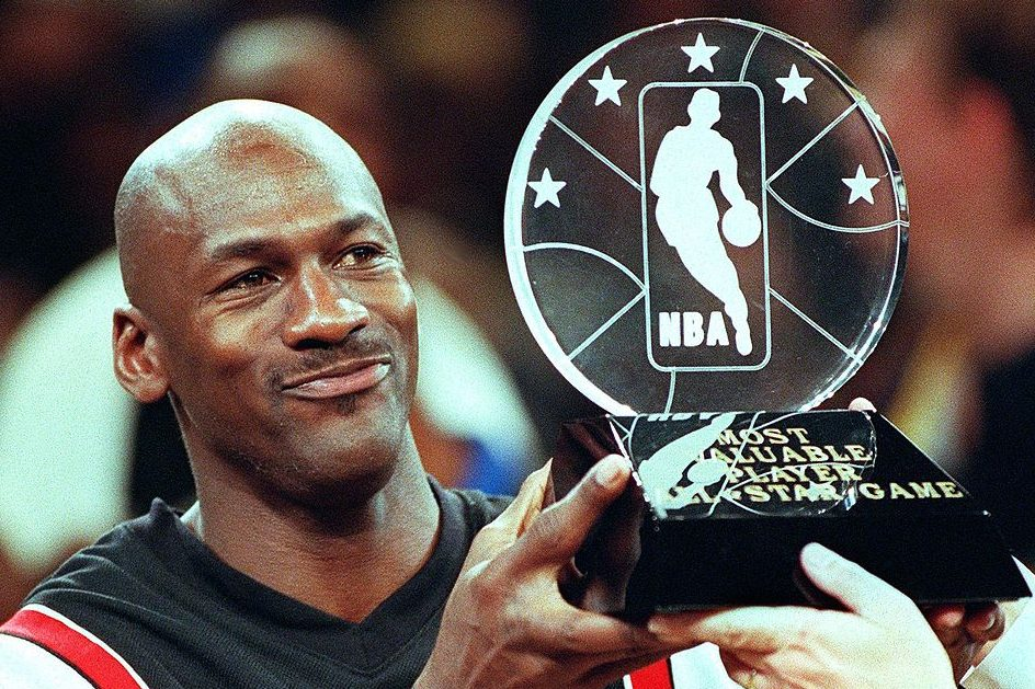 Michael Jordan holds up the Most Valuable Player trophy at the All-Star game. (TIM CLARY/AFP via Getty)