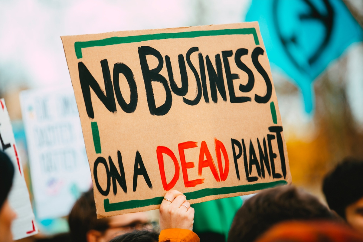 Holding up a protest sign at a climate change rally