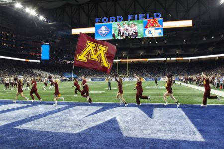 Minnesota cheerleaders run with the school logo flag across the end zone after a score during the Quick Lane Bowl game between the Minnesota Golden Gophers and the Georgia Tech Yellow Jackets on December 26, 2018 at Ford Field in Detroit, Michigan.  Minnesota defeated Georgia Tech 34-10.  (Photo by Scott W. Grau/Icon Sportswire via Getty Images)