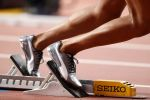 A runner settles into their starting blocks before a race