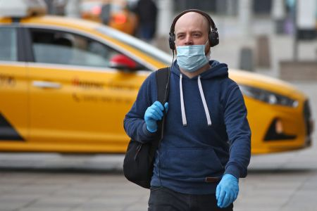 A man walks with a face mask on