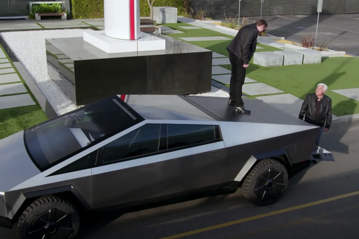 Elon Musk stands on the Cybertruck bed cover next to Jay Leno