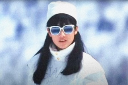 A Japanese woman poses on a ski slope.