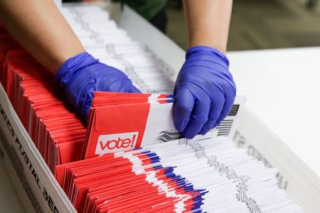 Election workers sort vote-by-mail ballots