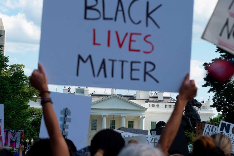 Demonstrators protesting the death of George Floyd hold up placards up near the White House on May 31, 2020 in Washington, DC.