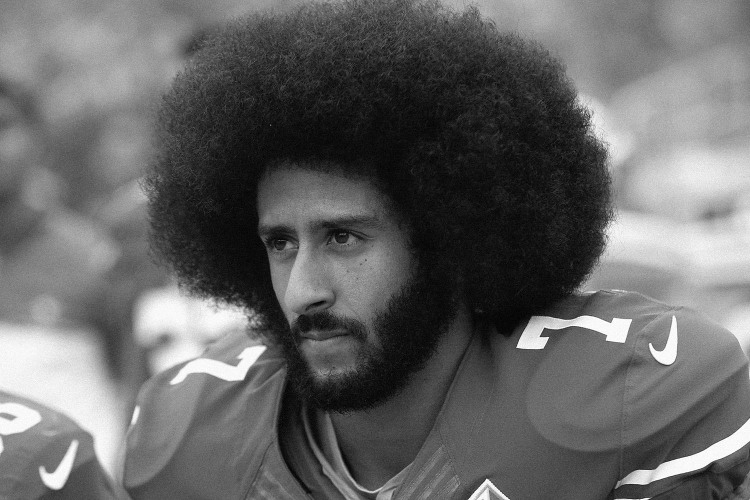 Colin Kaepernick kneels before a game
