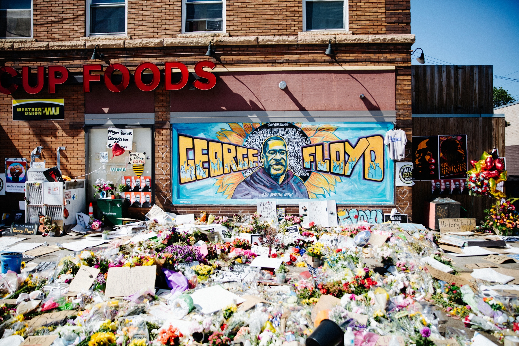Dozens of flower bouquets in front of the George Floyd memorial