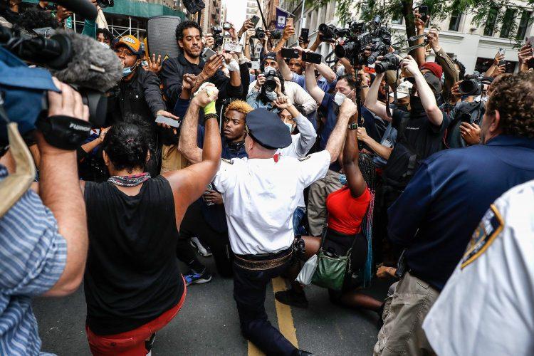 A police officer kneeling among protestors