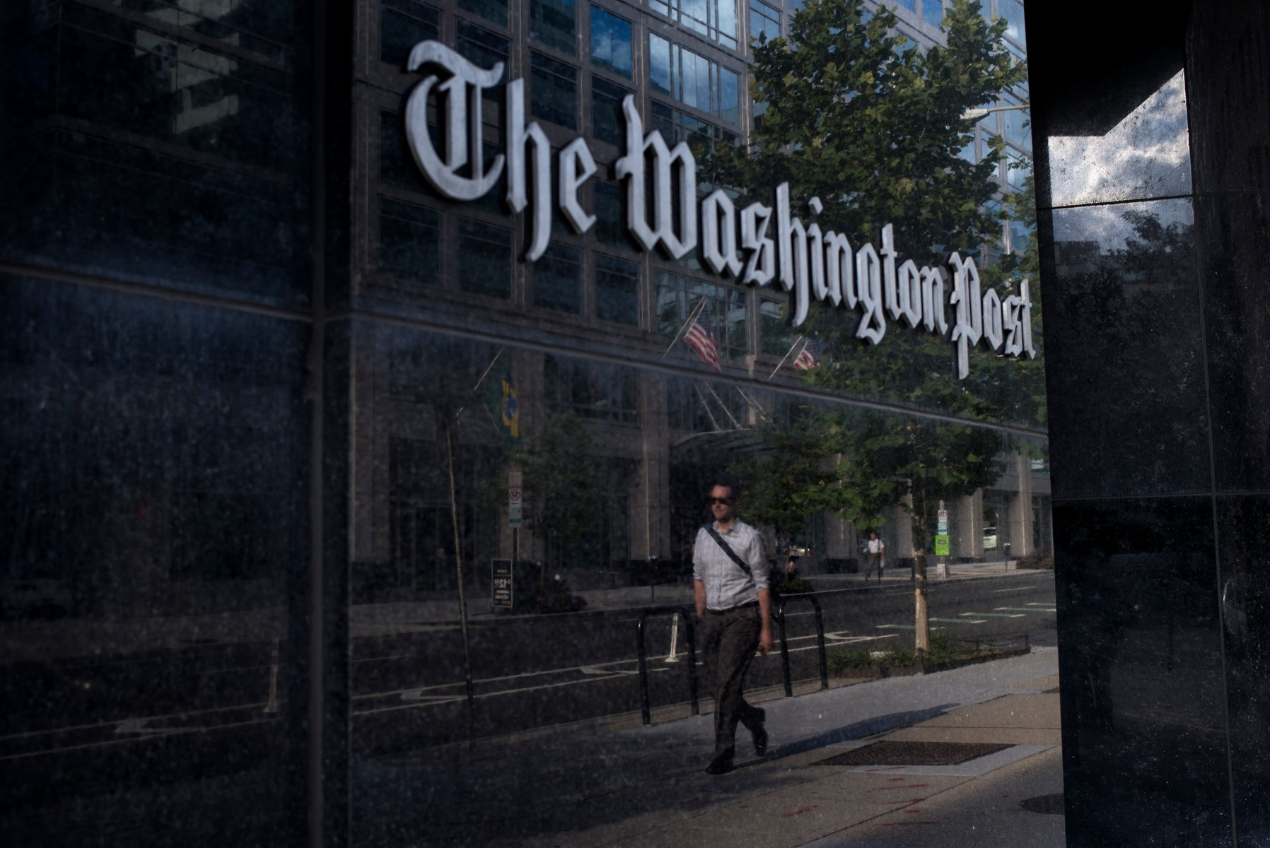 A man walks past The Washington Post. (Photo by BRENDAN SMIALOWSKI/AFP via Getty Images)