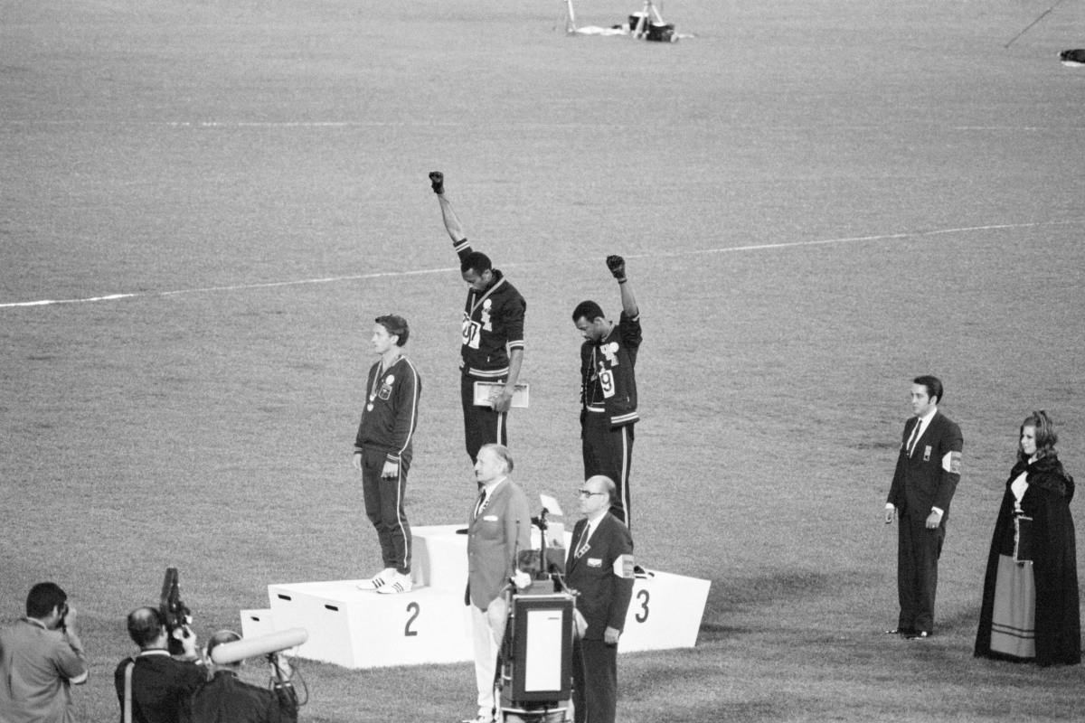 Tommie Smith and John Carlos, gold and bronze medalists in the 200-meter run at the 1968 Olympic Games, engage in a victory stand protest against unfair treatment of Black people in the United States.