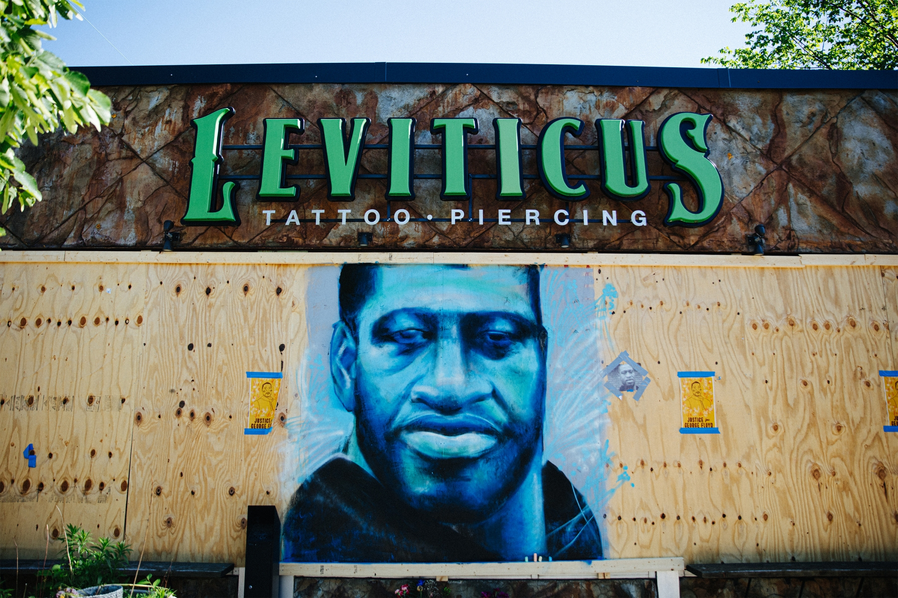 A blue and black portrait of George Floyd on Leviticus Tattoo and Piercing