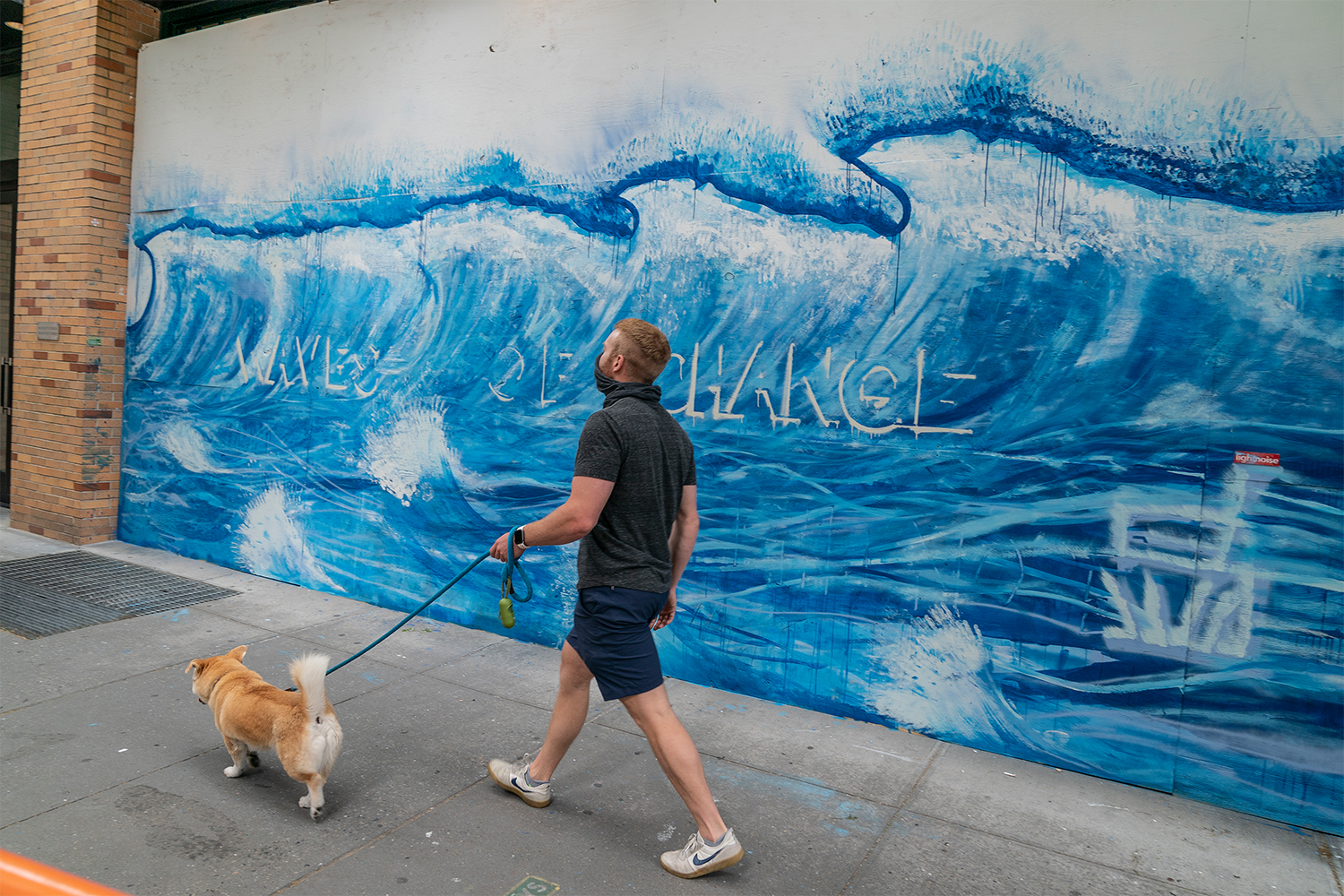 """A mural reads """"Waves of Change"""" on the plywood of Moschino in SoHo, NYC"""