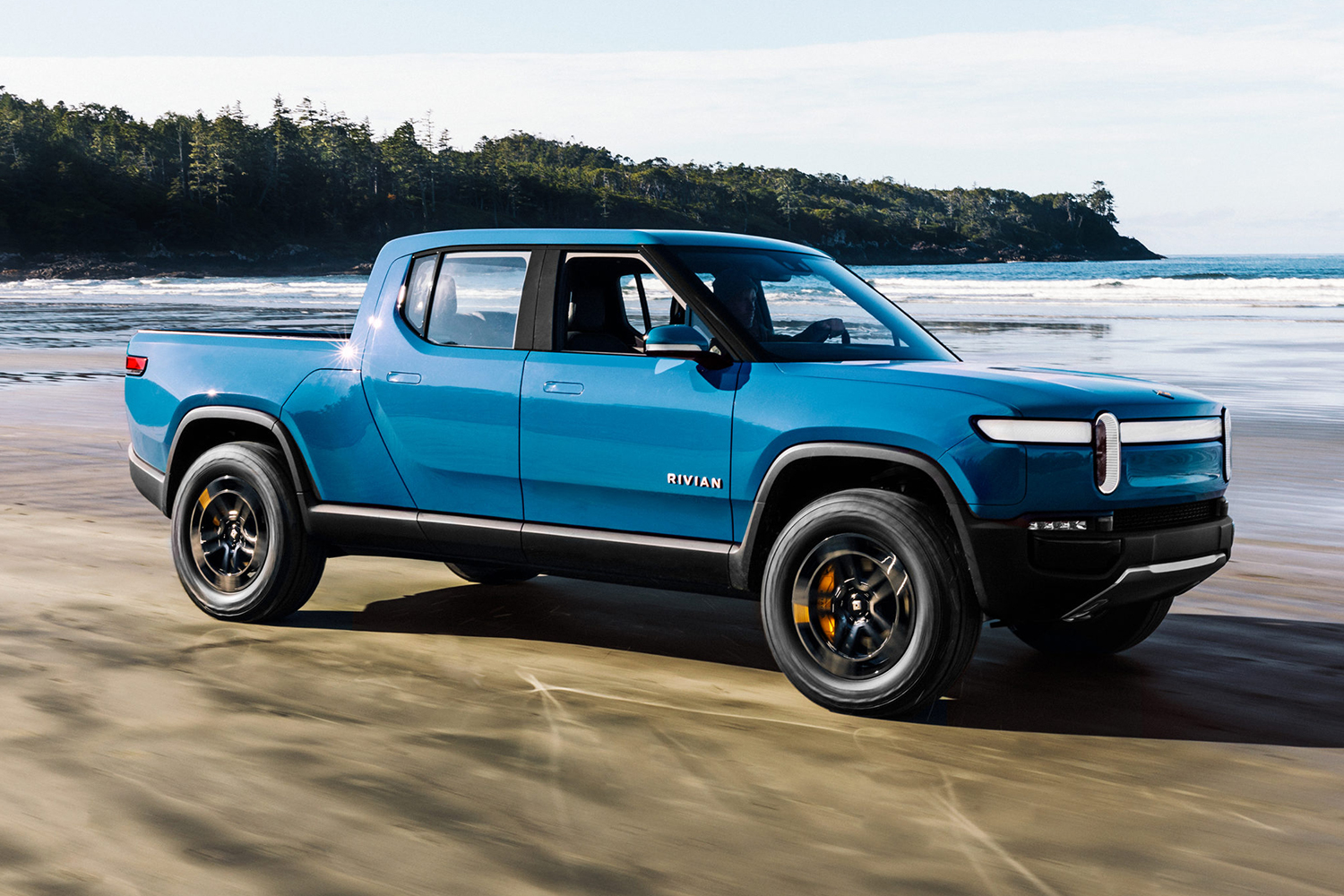 The Rivian R1T electric truck driving on the beach