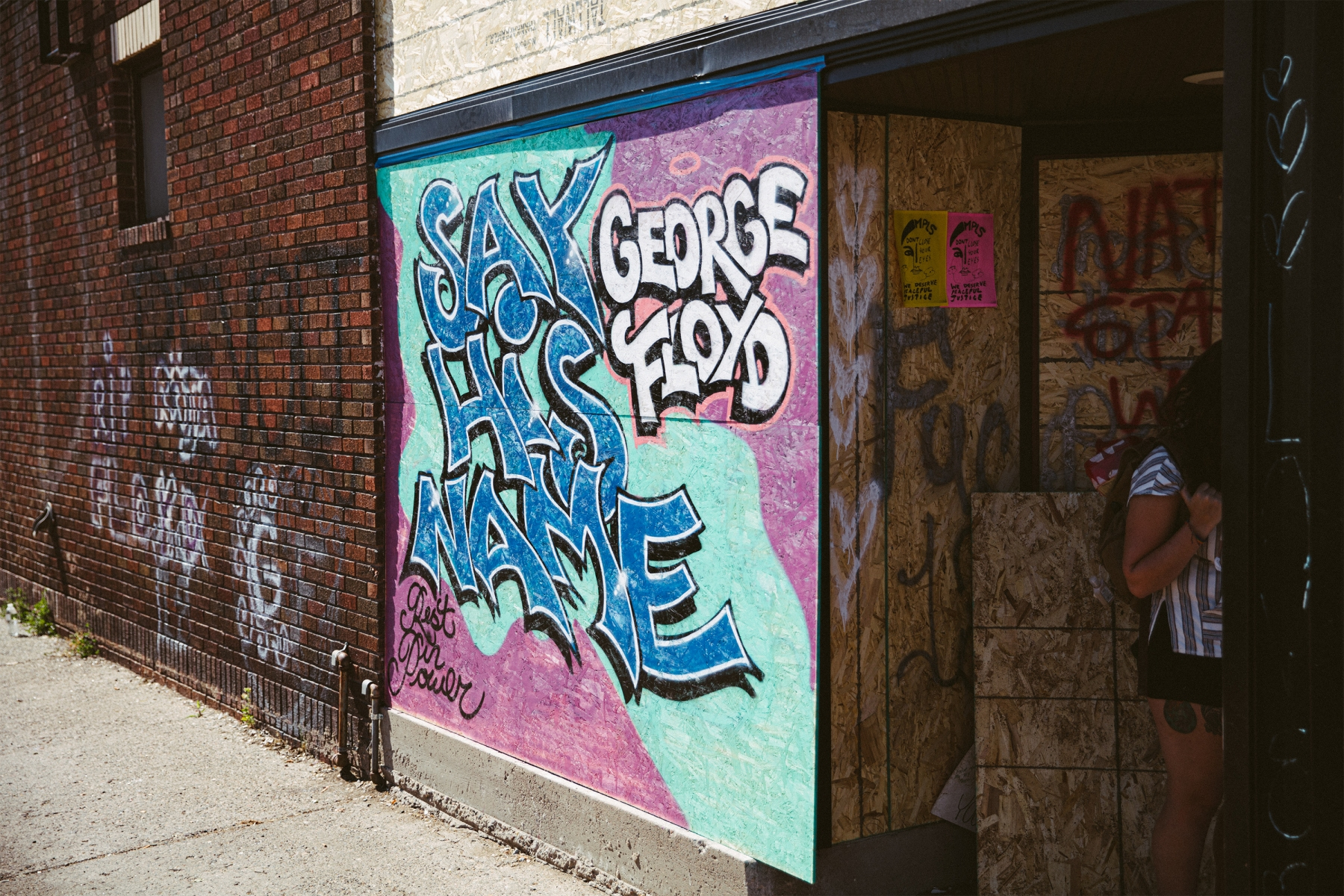 """Blue and purple graffiti in Minneapolis for George Floyd reading """"Say His Name"""