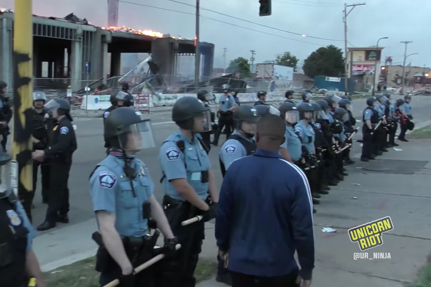 A black man walks in front of Minneapolis police officers during protests