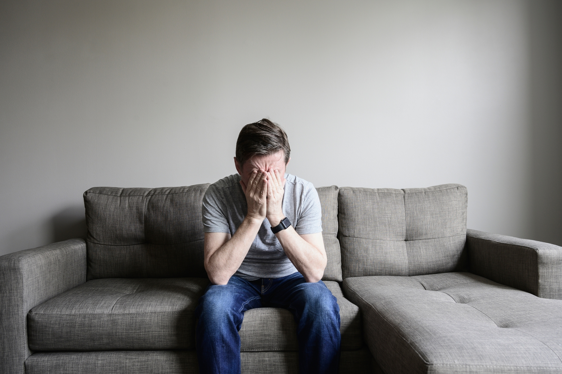 unhappy person sitting on couch in despair