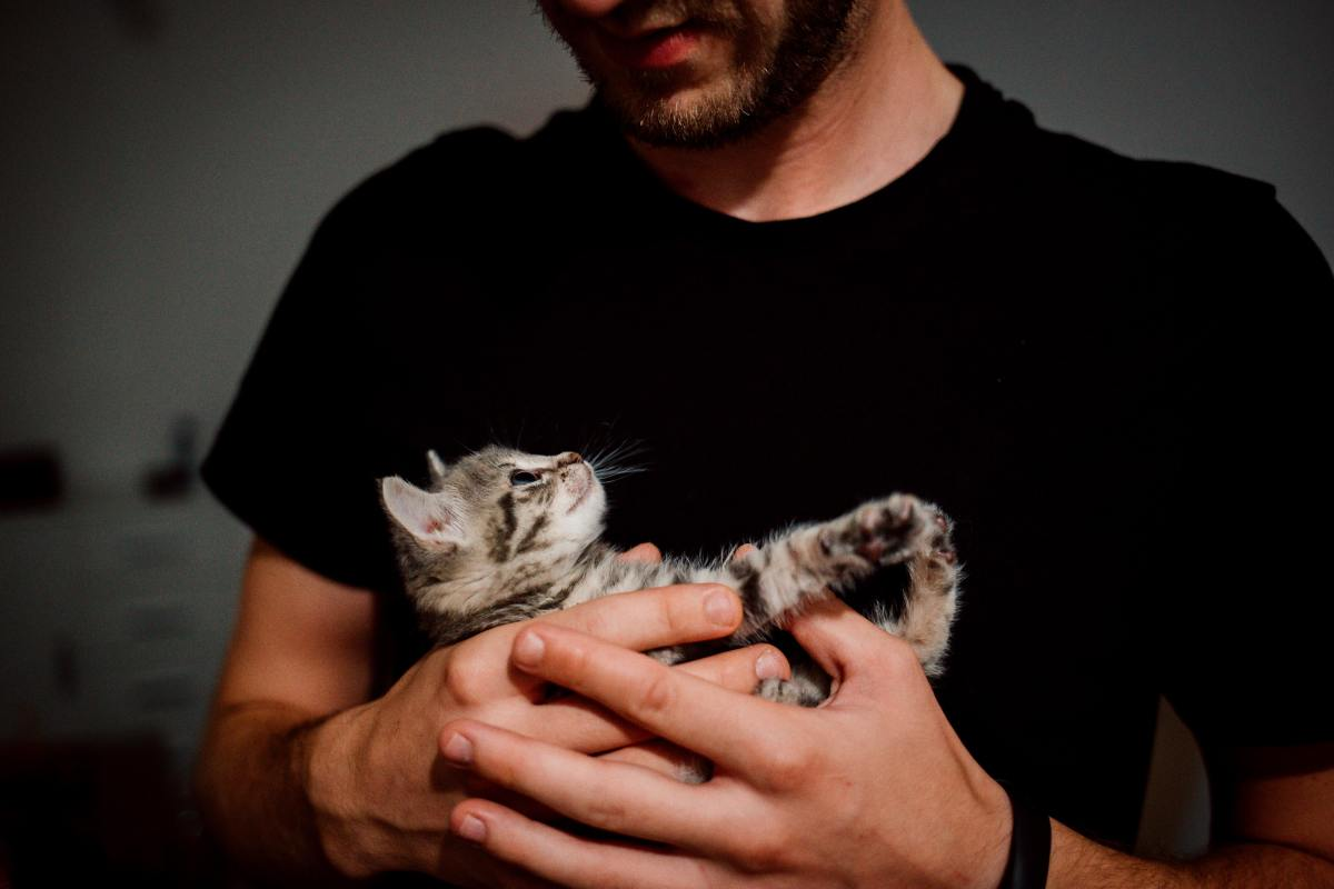 man cradling cat