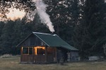 A rural cabin with smoke coming out of the chimney