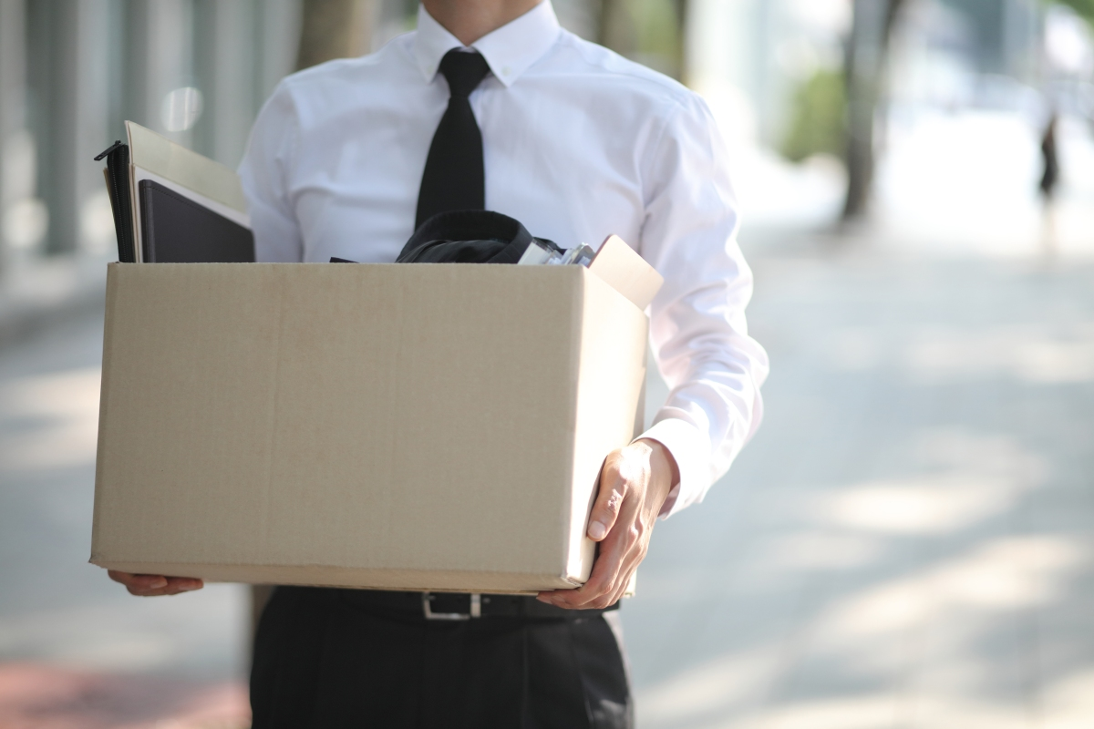 Person in a shirt and tie carrying a box