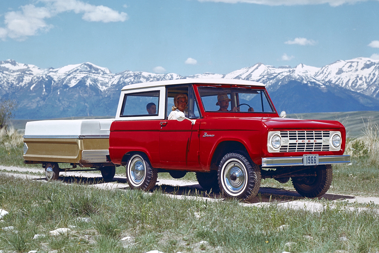 1966 red and white Ford Bronco towing a camper