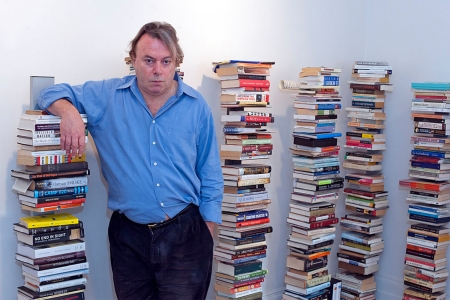 Christopher Hitchens standing next to piles of books