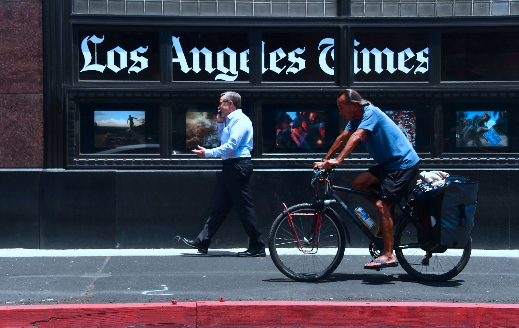 People make their way past the Los Angeles Times office building in downtown Los Angeles, California on July 16, 2018. (Photo by Frederic J. BROWN / AFP)