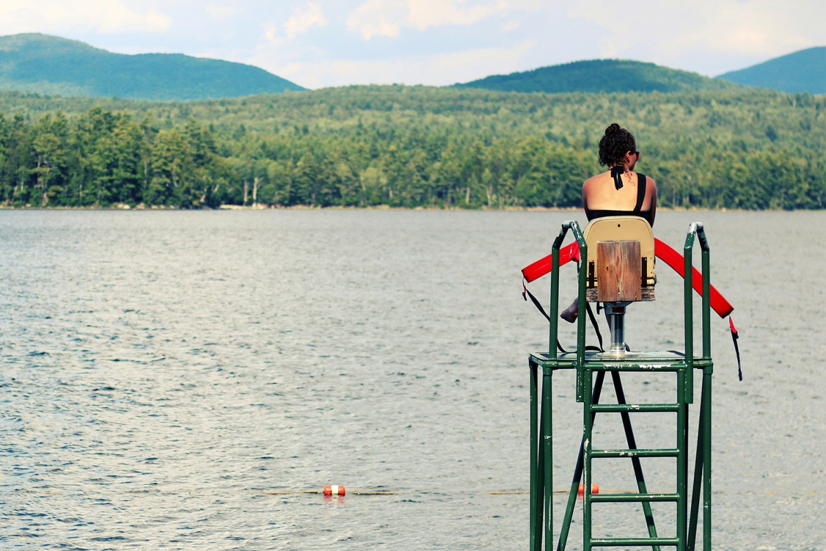 lifeguard sitting on a stand overlooking a lake