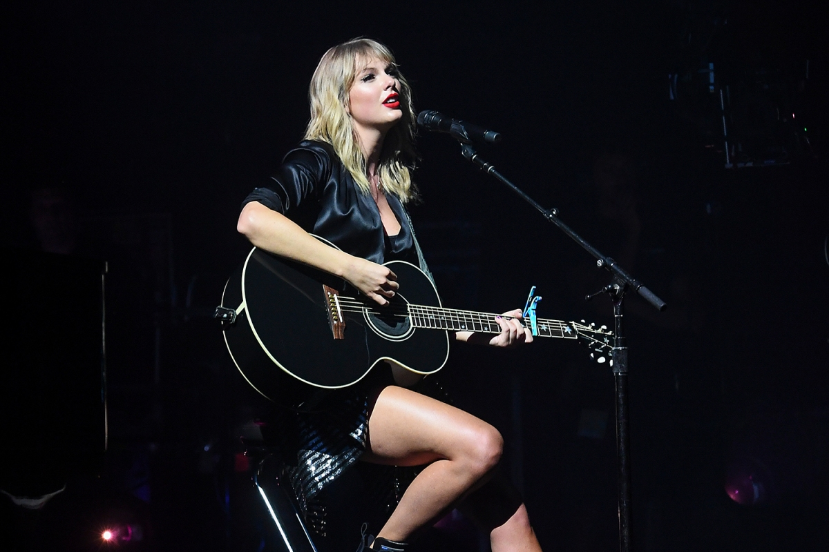 Taylor Swift in black playing a guitar at a concert