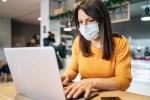 woman wearing a mask using a laptop computer