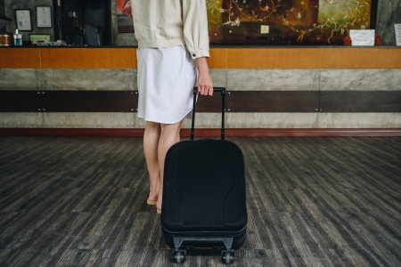 woman rolling a suitcase in a hotel lobby
