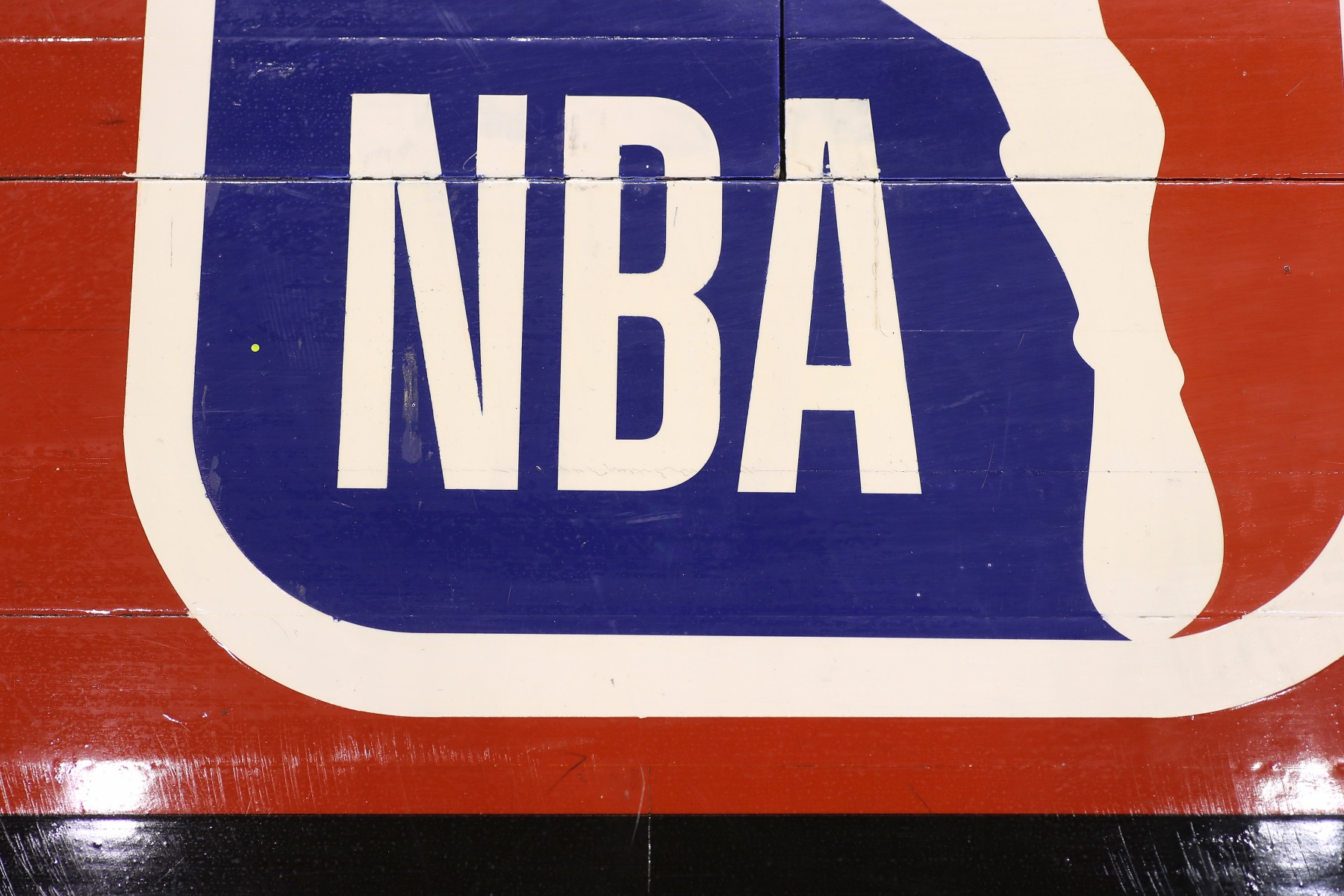 A detailed view of the NBA logo painted on the wooden floor boards of the court