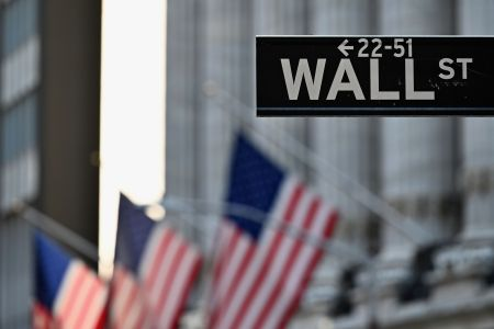 Wall Street sign in front of U.S. flags