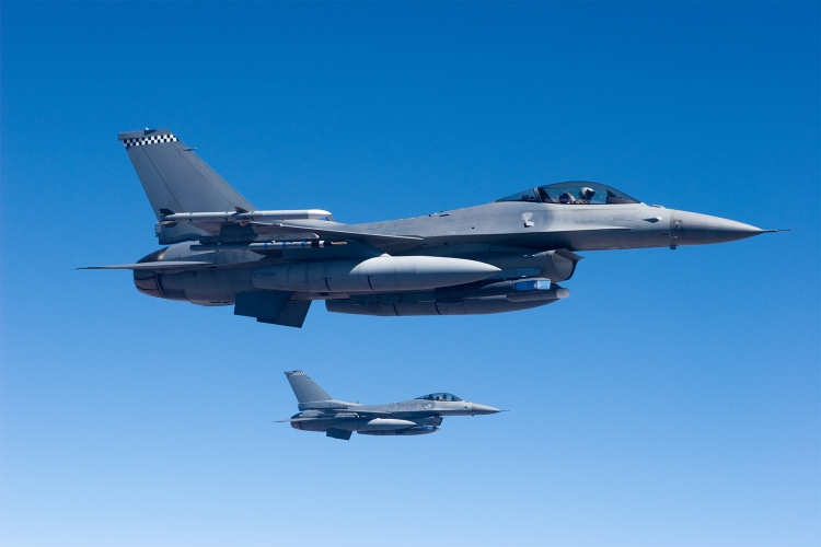 Two F-16 fighter aircraft flying in formation.