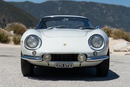 A white 1966 Ferrari 275 GTB Long Nose sitting on the road