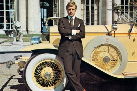 """Robert Redford as Jay Gatsby in the 1974 movie adaptation of """"The Great Gatsby"""" stands next to a yellow Rolls-Royce"""