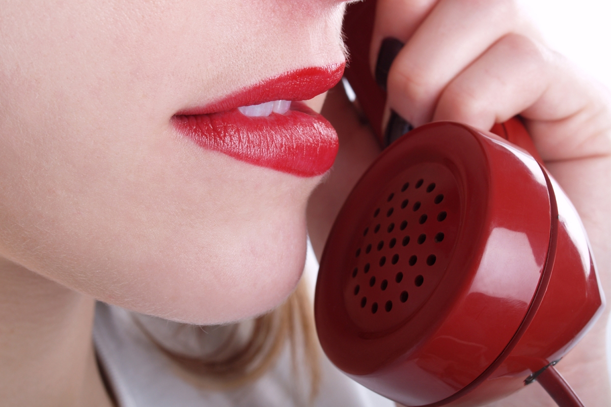 woman with red lipstick talking on the phone
