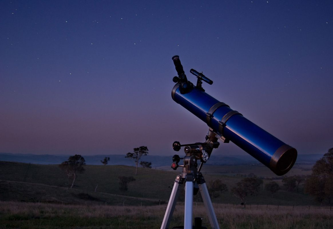 Telescope sitting in a field at dusk