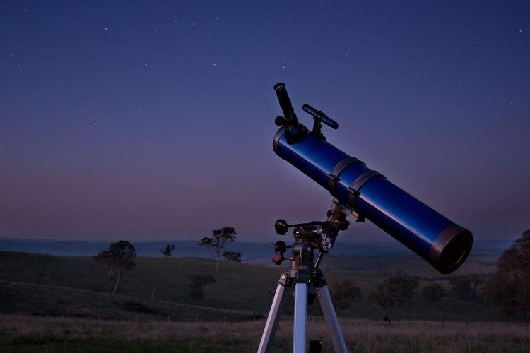 Telescope sitting in a field at dusk