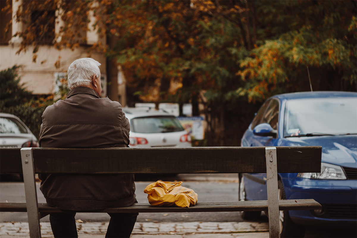 elderly man sitting by himself on a bench