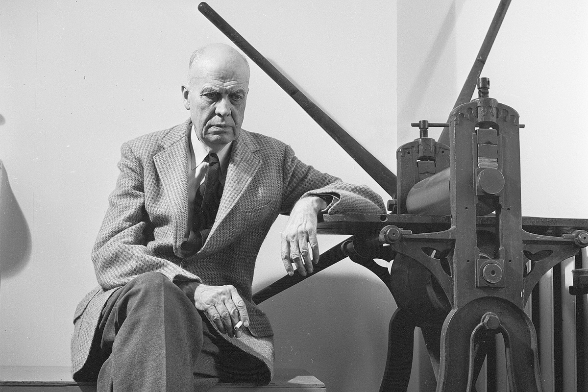 American realist painter Edward Hopper (1882-1967) sitting by a manual printing press in his Greenwich Village studio