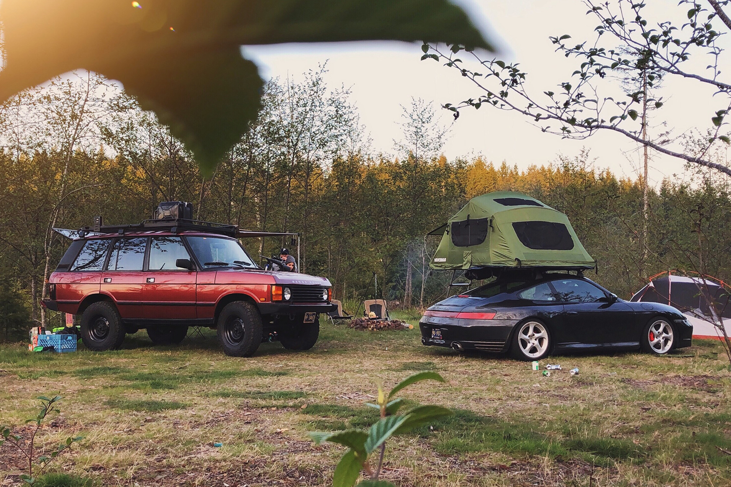 A 1991 red Range Rover Classic and black Porsche 996 with a car camping tent