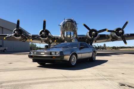DeLorean DMC-12 stainless steel car in front of an airplane